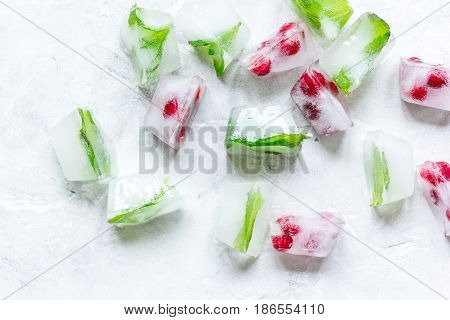 fresh mint and red berries in ice cubes on gray stone desk background top view