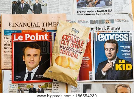 PARIS FRANCE - MAY 10 2017: Potato chips pack above multiple international newspapers front page covers with the picture of the newly elected French president Emmanuel Macron the 8th President of France