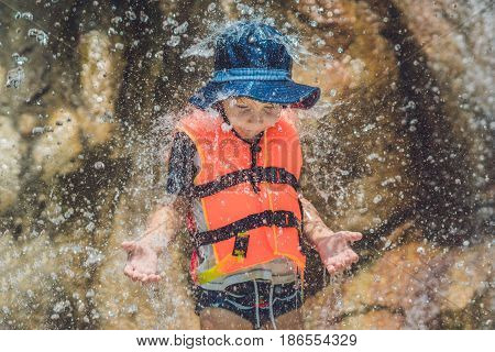 Young Boy Relaxing Under A Waterfall In Aquapark