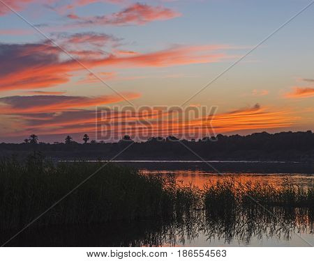 Beautiful Orange Sunset Sky Over River With Grass Reeds