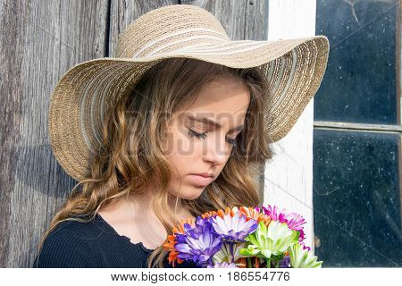 pretty teenage girl with summer hat and colorful daisy bouquet by barn window
