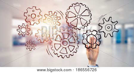 Close of businesswoman hand touching gears on screen with palm and office at background
