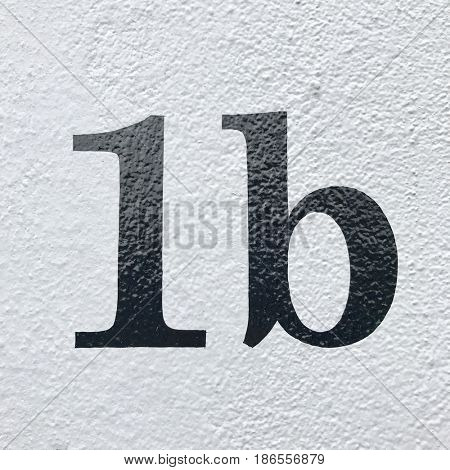Number 1b house number letter address sign painted black on white stone wall textured background