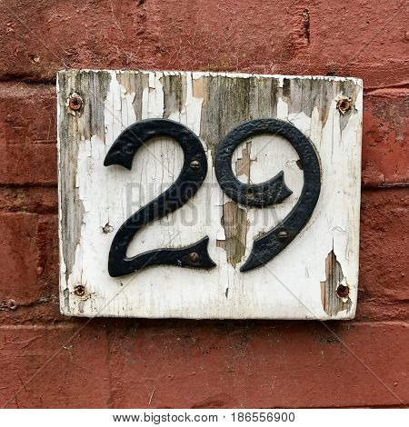 Number 29 twenty nine black metal house number address sign screwed into painted white   wood plaque on red brick stone wall textured background