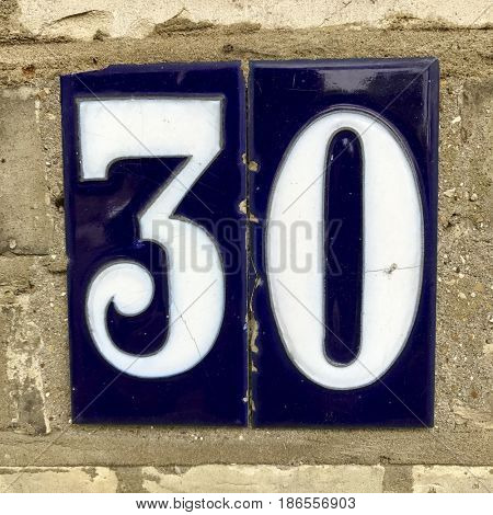 Number 30 thirty three zero blue tile house number address sign brick wall textured background