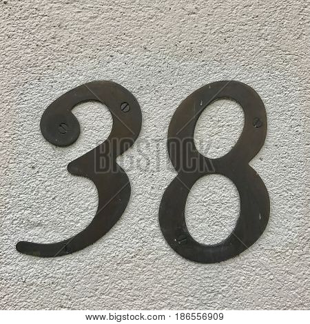 Number 38 thirty eight silver metal house number address sign screwed into painted white stone wall textured background