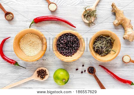 Cooking with spices, salt and pepper on kitchen wooden table background top view