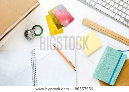 admission fee-paying school with credit cards, keyboard and notebook on white desk background top view mockup
