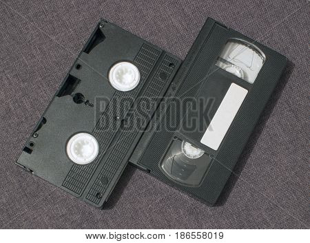 Two video cassettes lie side by side with the front and back sides