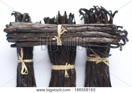 Four fresh bunches of Madagascar vanilla pods against a white background. Food grade and a great promo for articles or recipe ingredients list websites.