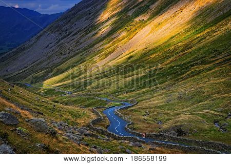 A winding empty road through a valley amidst a green scenery backdrop.