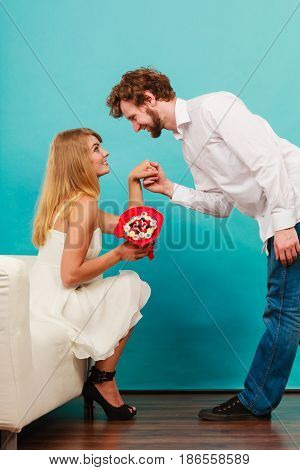 Handsome man giving pretty woman candy bunch flowers. Young boyfriend with present gift kneeling in front of girlfriend. Happy loving couple. Love.