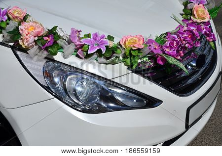 A Detailed Photo Of The Hood Of The Wedding Car, Decorated With Many Different Flowers. The Car Is P