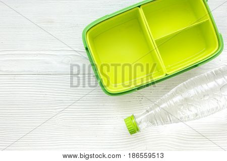green lunchbox and bottle of water for healthy food dinner at school on white wooden table background top view mockup