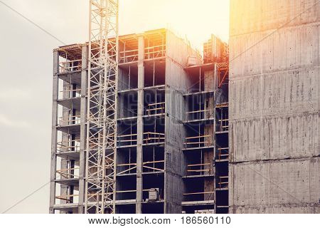 Building a house of panel concrete slabs with a crane. Reinforced concrete. Concept building of new houses from combined materials. Flare, sun.