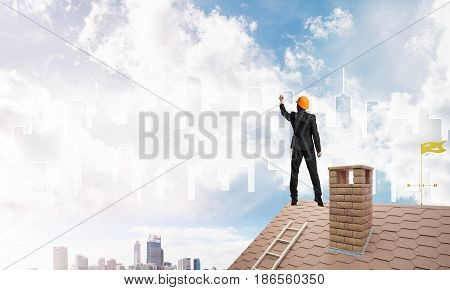 Engineer man standing with back on house roof and drawing city. Mixed media