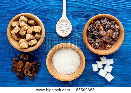lumps and sanding sugar for cooking sweets on blue kitchen table background top view