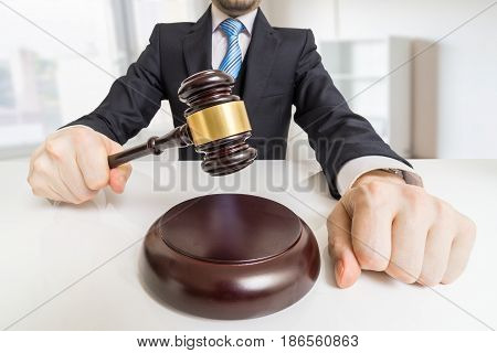 Young man in suit with gavel in office. Auction or justice concept.
