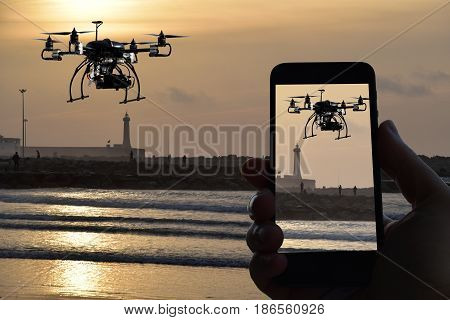 Drone , remote control from smartphone , sunset over the sea whit watchtower background