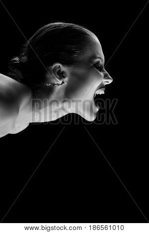 angry nude girl screaming on black background, monochrome