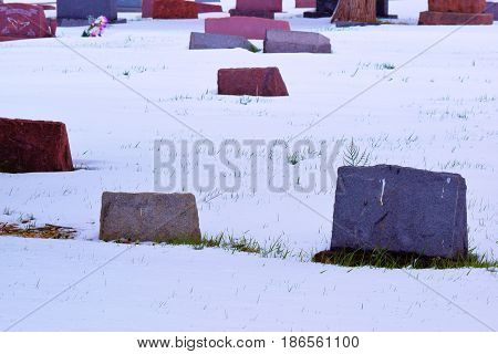 Old colorful grave headstones taken in a cemetery surrounded by snow