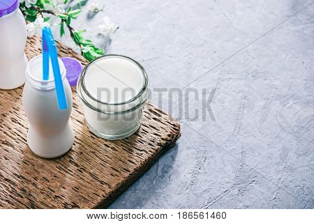 White bottles and glass jar of liquid dairy product such as yoghurt or buttermilk. Concrete background with wooden trivet and plum tree flowers. Selective focus