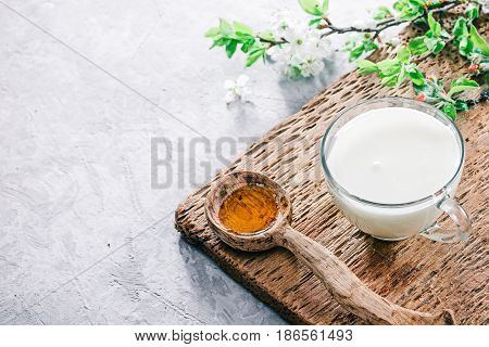 Buttermilk in glass cup with heart cookies and honey. Concrete background with wooden trivet and plum tree flowers. Selective focus