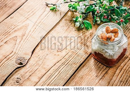 Homemade ricotta with red marmalade and almond nuts in glass jar. Raw wood background with apple and plum blooming twigs. Selective focus