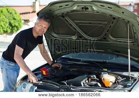 Oil change in car. Man repairing the engine in the car. Self-changing oil in own car. Man looks under the hood of his auto