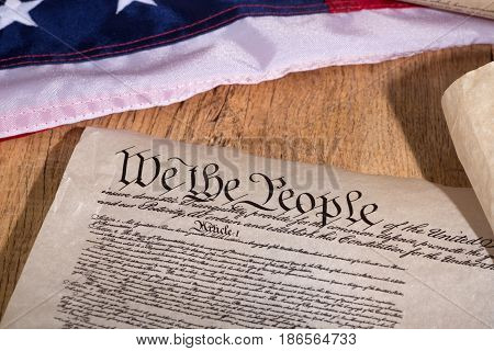 United States constitution with flag on a wood surface