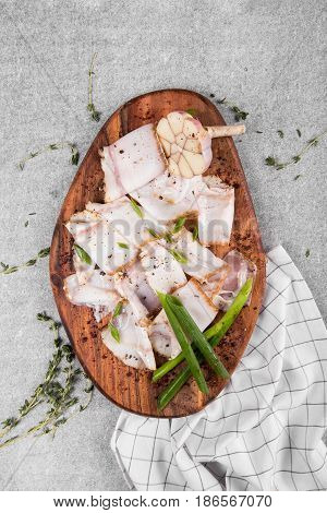 tasty bacon with spices on wooden cutting board on a gray background. flat lay. copy space.