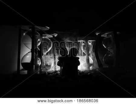 Time And Love Concept. Silhouettes Of Toy Ceramic Figures Hugging Between Hourglasses In Dark Lighte