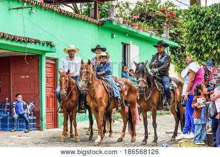 San Juan del Obispo, Guatemala - June 12 2016: Cowboys ride horses in horse street parade in village near Antigua, Guatemala
