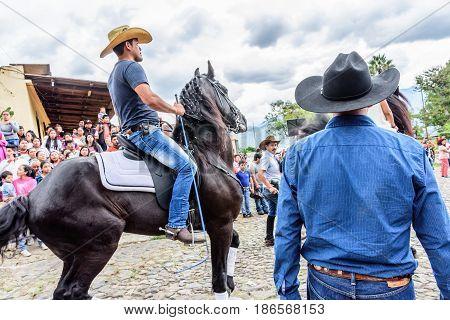 San Juan del Obispo, Guatemala - June 12 2016: Cowboys ride horses in horse street parade in village near Antigua, Guatemala