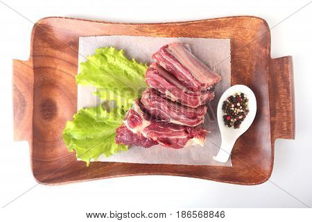 Raw beef edges, lettuce leaf and spices on wooden desk isolated on white background from above and copy space. ready for cooking