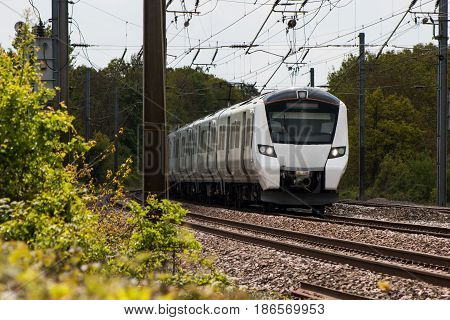 White electric passenger train in motion on the railway