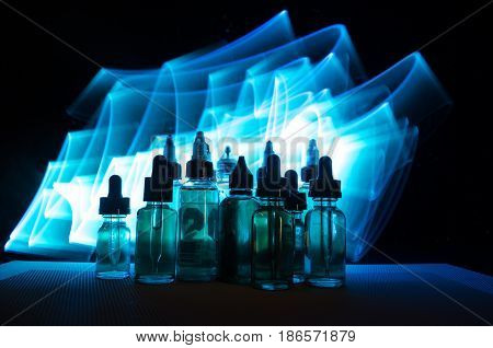 Vape Concept. Smoke Clouds And Vape Liquid Bottles On Dark Background. Light Effects.