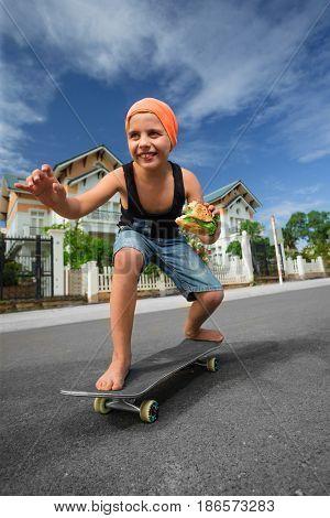 Hungry boy skating and eating hamburger