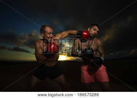 Strong boxer doing  kickboxing exercise with trainer at sunset