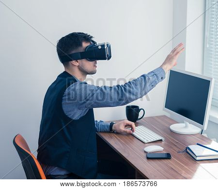Young businessman in vr glasses drawing chart with gesture. Virtual reality in office