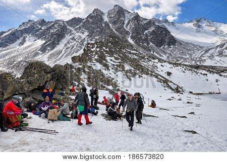 MUNKU-SARDYK BURYATIA RUSSIA - April 29 2017: Climbers are resting at foot of mountain before rising to peak. Favorable weather promotes good mood among athletes