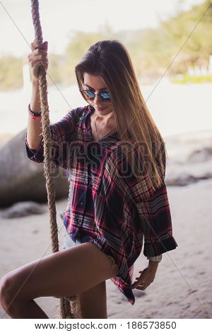 Cute girl posing on a beach. She holds a rope and looking far away. Perfect photo for a fashion store.