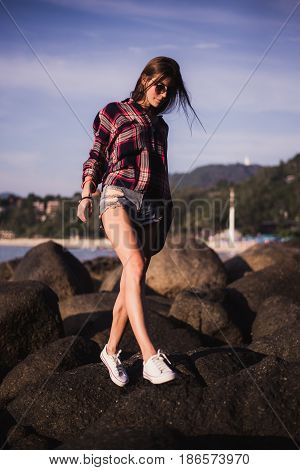 Sexy Girl in flannel shirt on the rocky beach