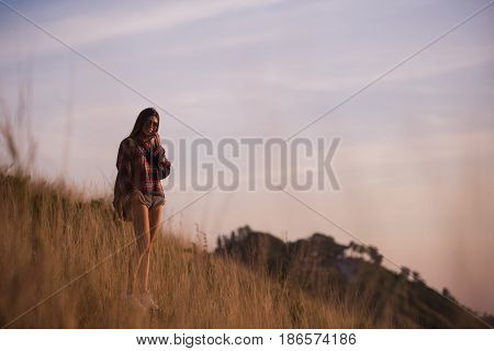Summer sunny lifestyle fashion portrait of young stylish hipster woman walking in mountains, wearing cute trendy outfit, smiling enjoy weekends, travel with backpack. Awesome ocean view on a background