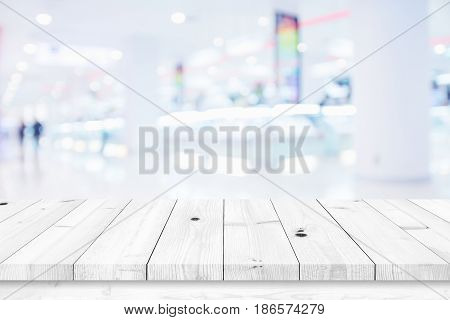 White wood table with blur shopping mall background. For display or montage your products.