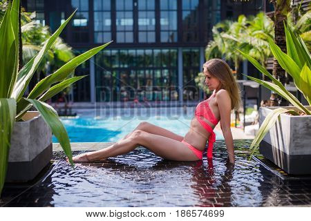 Spending summer time poolside. Rear view of young woman in bikini sitting by the poolside.