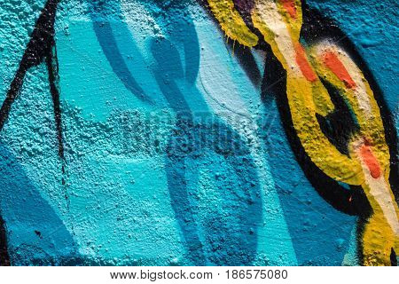 Close up of blue, white, orange, yellow and black graffiti with chain links on a brick wall