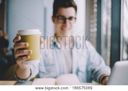 Handsome young man having lunch in cafe alone. Attractive guy showing a cup of coffee right to the camera. He is really delighted. Cup is in focus