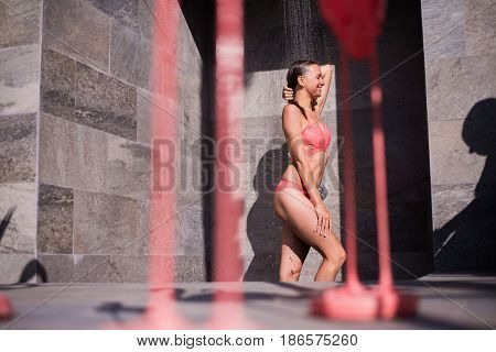 Attractive sexy woman under the shower outdoors near swimming pool at luxury hotel resort.