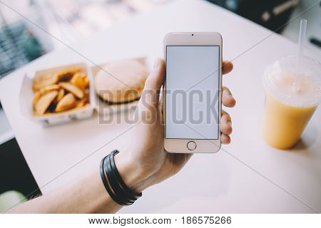 Young man's hand holding mobile phone. He is sitting in cafe and having his meal while searching for some information. Place for your advert or logo. Close up. Horizontal position of the phone